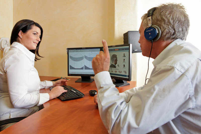 An audiologist sitting behind a desk examining a patient