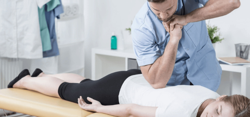 A chiropractor kneading patient's back muscles
