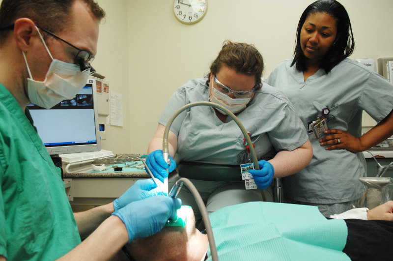 Two dental assistants assisting a dentist