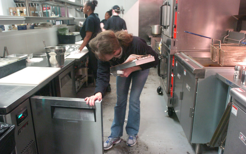 A female environmental health officer inspecting a restaurant kitchen