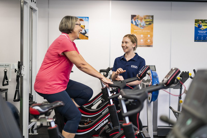 An exercise physiologist talking with an elderly woman on stationary bicycle