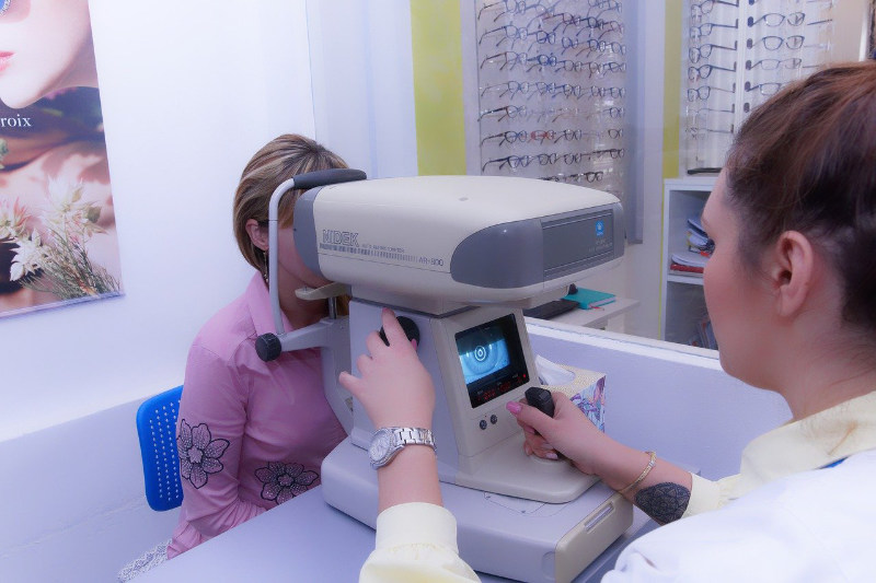 An optometrist examining patient's eyesight with an ophthalmoscope