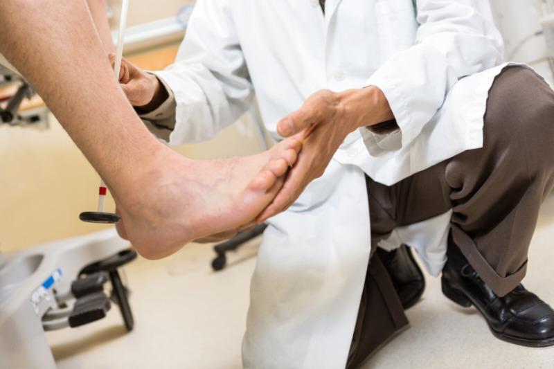 A pedorthist examining patient's foot