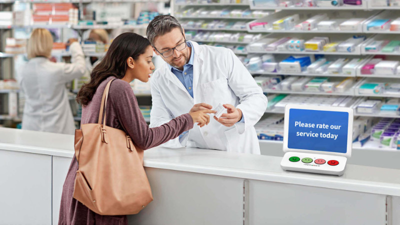 A male pharmacy technician behind a counter counseling a client in a drug store