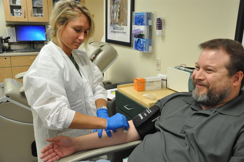 A phlebotomist drawing blood from a patient